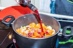 Męska ręki mienia butelka i dolewania czerwone wino w niecki potrawkę z smażyć marchewki i cebule na nowożytny elektrycznym Fotografia Stock