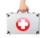 Męska ręki mienia equipments bagażu pierwsza pomoc odizolowywał białych półdupki Fotografia Stock