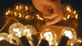 Męska ręki zmiany elektrycznego luzowania retro girlanda Przemysłowa żarówka Zdjęcie Stock