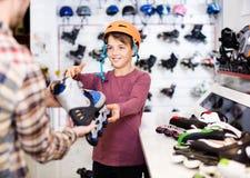 Męska sklepowego asystenta pomaga chłopiec wybierać wrotki w sporcie Obraz Royalty Free