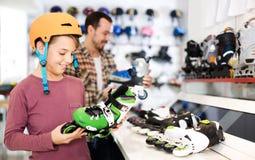 Męska sklepowego asystenta pomaga chłopiec wybierać wrotki w sporcie Fotografia Stock