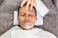Męska twarz z śmietanki maską, ręki fachowy beautician Zdjęcie Royalty Free