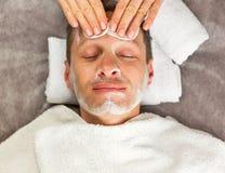 Męska twarz z śmietanki maską, ręki fachowy cosmetologist Zdjęcia Stock