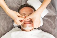 Męska twarz z śmietanki maską, ręki fachowy cosmetologist Obrazy Stock
