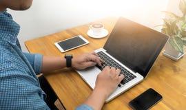 Męski łysy studencki obsiadanie przy drewnianym biurkiem i używać cyfrowego compu Zdjęcie Royalty Free