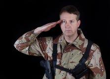 Męski żołnierz daje salutowi podczas gdy pod rękami Zdjęcia Stock