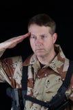Męski żołnierz salutuje podczas gdy pod rękami obrazy royalty free