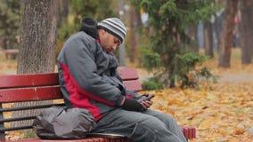 Męski alkoholu nałogowiec ma drzemkę na ławce w jesień parku z butelką w ręce zbiory