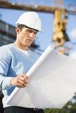 Męski architekt egzamininuje projekt przy budową Obrazy Stock