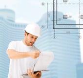 Męski architekt patrzeje projekt w hełmie Zdjęcie Stock