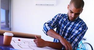 Męski architekt pracuje na projekcie nad brulionowość stołem 4k zbiory