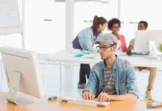 Męski artysta używa komputer z kolegami wewnątrz przy biurem Zdjęcia Royalty Free
