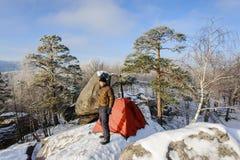 Męski arywista prawie jego namiot na wierzchołku skała Obrazy Stock