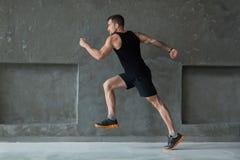 Męski atleta szybkobiegacza bieg, ćwiczy indoors obrazy royalty free