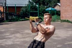 Męski atlety zakończenie, pociąg natura miasto, lata trx szkolenie, Balansowa motywacja, garbnikująca skóra w skrótach ćwiczenie Fotografia Stock