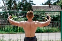 Męski atlety zakończenie, pociąg natura miasto, lata trx szkolenie, Balansowa motywacja, garbnikująca skóra w skrótach ćwiczenie Zdjęcie Stock
