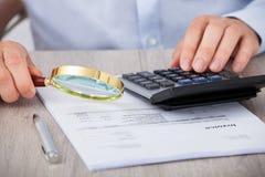 Męski audytor dokładnie badać pieniężnych dokumenty fotografia royalty free