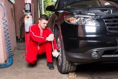Męski auto mechanika śrubowanie lub odśrubowania samochodowy koło wyrwaniem Fotografia Royalty Free