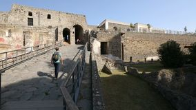 Męski backpacker kamienny przejście w kierunku wejścia Pompeii na słonecznym dniu iść up zbiory