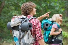 Męski backpacker pokazuje coś kobieta w lesie Zdjęcia Royalty Free