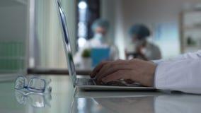 Męski badacza otwarcia laptop i przymknięcie po pisać na maszynie, stażyści przy tłem zbiory
