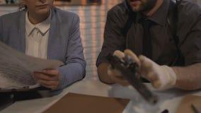 Męski balistyka ekspert sprawdza pojemność pistolet od miejsca przestępstwa, milicyjna praca zbiory