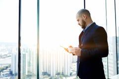 Męski bankowiec stoi z filiżanką kawy w ręce w biurowym wnętrzu przeciw okno z kopii przestrzenią Fotografia Stock