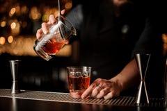 Męski barman nalewa alkoholu koktajl z durszlakiem obrazy stock