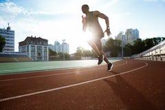Męski biegacz ćwiczy jego sprint w atletyki stadium torze wyścigów konnych Zdjęcie Royalty Free