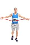 Męski biegacz krzyżuje metę Zdjęcia Royalty Free