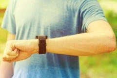 Męski biegacz patrzeje jego mądrze zegarek outside Zdjęcie Stock