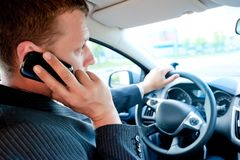 Męski biznesmen opowiada na telefonie komórkowym podczas gdy jadący obraz stock