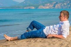 Męski biznesmena lying on the beach na plaży Obraz Stock