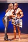 Męski bodybuilder świętuje jego mistrzostwa zwycięstwo na scenie Zdjęcia Stock