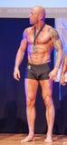 Męski bodybuilder świętuje jego mistrzostwa zwycięstwo na scenie Obraz Stock