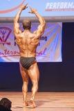 Męski bodybuilder napina jego mięśnie i pokazuje jego najlepszy budowę ciała Zdjęcia Stock