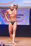 Męski bodybuilder napina jego mięśnie i pokazuje jego najlepszy budowę ciała Obraz Stock