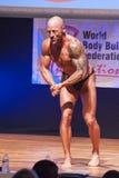 Męski bodybuilder napina jego mięśnie i pokazuje jego najlepszy budowę ciała Zdjęcia Royalty Free
