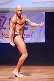 Męski bodybuilder napina jego mięśnie i pokazuje jego najlepszy budowę ciała Obraz Royalty Free