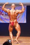 Męski bodybuilder napina jego mięśnie pokazywać jego budowę ciała Fotografia Stock