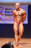 Męski bodybuilder napina jego mięśnie pokazywać jego budowę ciała Obrazy Royalty Free