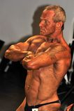 Męski bodybuilding konkursant pokazuje jego klatki piersiowej pozę Zdjęcie Stock