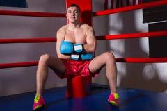 Męski bokser siedzi blisko czerwonego cor z nagą klatką piersiową w bokserskich rękawiczkach Obraz Stock