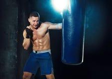 Męski boksera boks w uderzać pięścią torbę z dramatycznym zirytowanym oświetleniem w ciemnym studiu Zdjęcia Royalty Free
