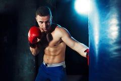 Męski boksera boks w uderzać pięścią torbę z dramatycznym zirytowanym oświetleniem w ciemnym studiu Zdjęcia Stock