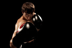 Męski boksera boks w uderzać pięścią torbę z dramatycznym zirytowanym oświetleniem w ciemnym studiu Zdjęcie Stock