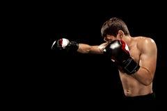Męski boksera boks w uderzać pięścią torbę z dramatycznym zirytowanym oświetleniem w ciemnym studiu Obraz Stock