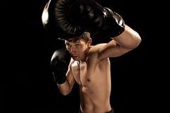 Męski boksera boks w uderzać pięścią torbę z dramatycznym zirytowanym oświetleniem w ciemnym studiu Fotografia Royalty Free