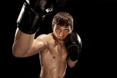 Męski boksera boks w uderzać pięścią torbę z dramatycznym zirytowanym oświetleniem w ciemnym studiu Obrazy Stock