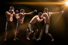 Męski boksera boks w uderzać pięścią torbę z dramatycznym zirytowanym oświetleniem w ciemnym studiu Obrazy Royalty Free